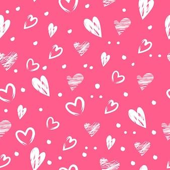 白い手描きのハートとバレンタインデーのお祭りの装飾のシームレスなパターン