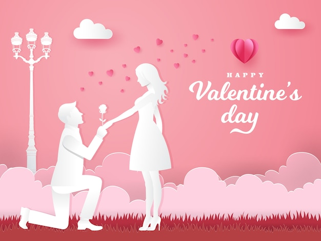 Valentine's day greeting card. young man kneeling to his girlfriend and giving a rose on the park with heart and pink background