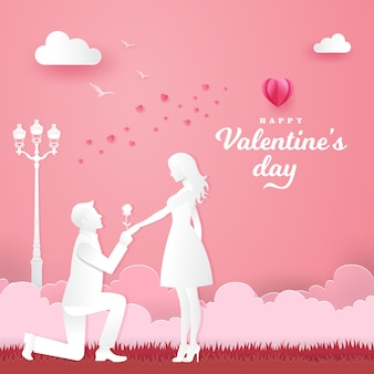 Valentine's day greeting card. young man kneeling to his girlfriend and giving a rose on the park with heart and pink