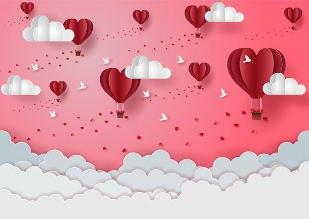 Valentine's day with floating balloons in the pink sky above the white clouds