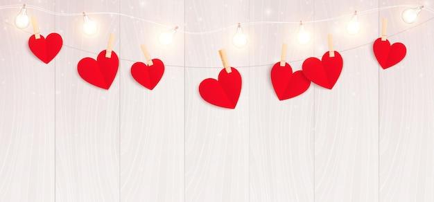 紙のイラストの心をぶら下げてライトストリングの水平方向のビューとバレンタインデーの心の現実的な構成