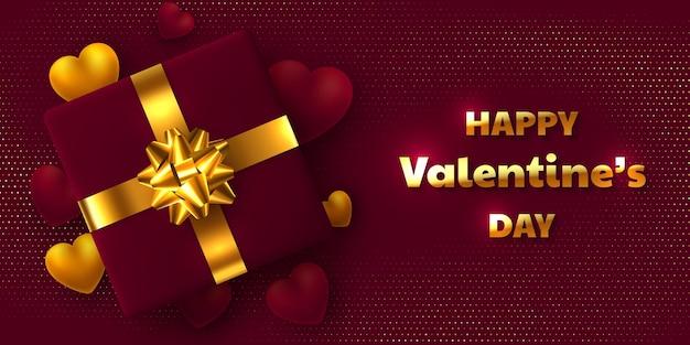 Дизайн праздника дня святого валентина. подарочная коробка с золотым бантом, 3d сердцами и текстом приветствия.
