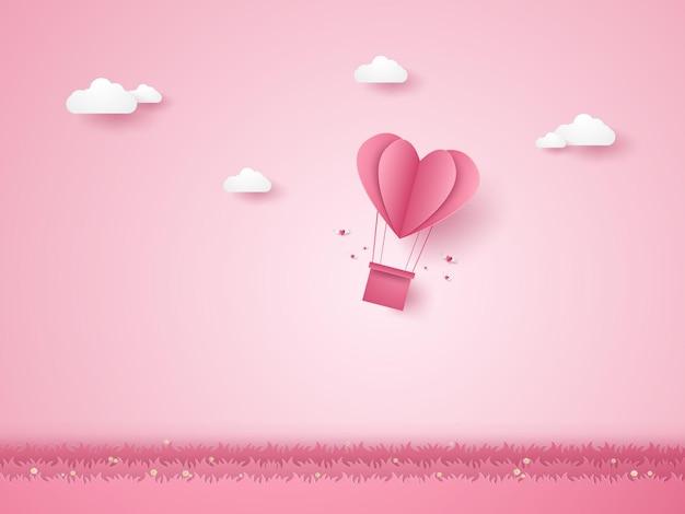 バレンタインデー草の上を飛んでいる愛のピンクのハートの熱気球のイラスト