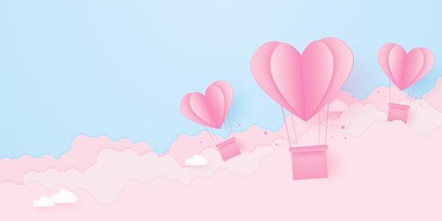 バレンタインデーの愛のコンセプトペーパーピンクのハート型の熱気球が雲と空に浮かぶ