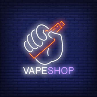 Vape shop neon sign. Hand holding electronic cigarette on brick wall.