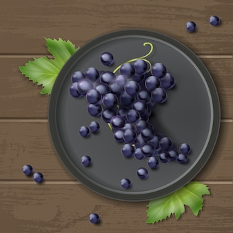 Vector bunch of grapes on plate with leaves, isolated on wooden background, top view