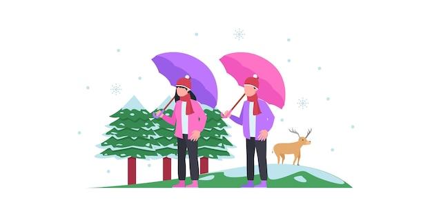 雪と2人が立っている冬の都市公園のベクトルイラスト。冬の都市公園のベンチ、フラット漫画スタイルの冬の休日のコンセプト
