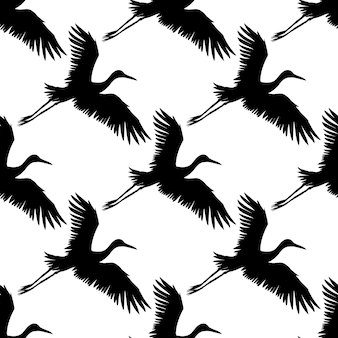 黒い手描きの空飛ぶ鶴鳥のシルエットのベクトルのシームレスなパターン