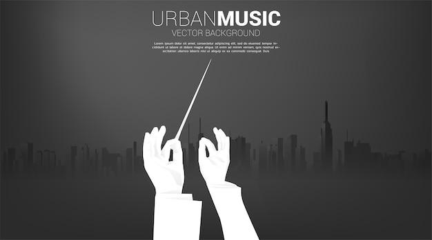 都市の背景を持つ指揮者の手のベクトルシルエット。音楽の街のコンセプト。