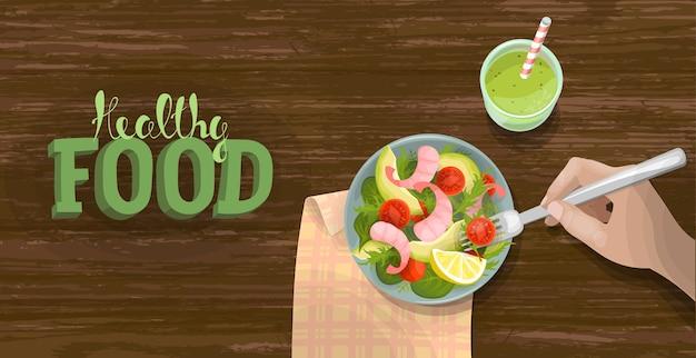 野菜とエビの新鮮なサラダボウルのスムージーの上面図。フィットネス配給ダイエットバナーテンプレート。木製のテーブルの背景にトマト、アボカド、レタス。健康食品のレタリング