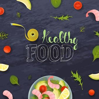 野菜とエビの新鮮なサラダボウルの上面図。フィットネス配給ダイエット巻尺。トマト、アボカド、チョークボードの背景にレタス。健康食品のレタリング