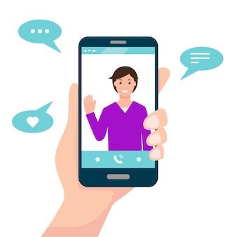 화상 통화 또는 통신 앱 개념. 인간의 손으로 화면에 남자와 스마트 폰 개최.
