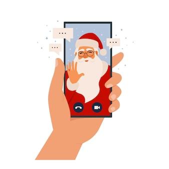 ビデオ通話サンタクロース、モバイルアプリでオンラインチャット。スマートフォンを持っている手。デバイスの画面でサンタさんが電話をかけています。