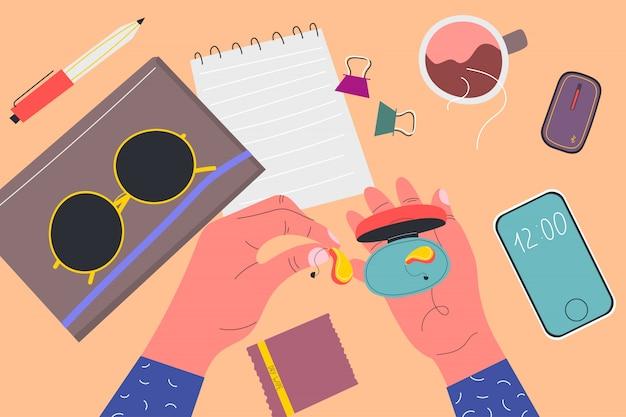 Вид сверху. мужская держит коробку из-под слухового аппарата. блокноты, солнцезащитные очки, телефон, салфетка, ручка, зажимы, чашка чая, прибор. красочные иллюстрации в плоском мультяшном стиле.