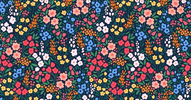 ヴィンテージの花の背景。濃い青の背景に小さな色とりどりの花でシームレスな花柄