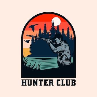 銃の狩猟と冒険のエンブレムバッジを持つヴィンテージハンター
