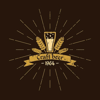 Винтажный логотип пива. пивоваренный завод. пивной стакан, листья хмеля и текст на ленте на коричневом фоне
