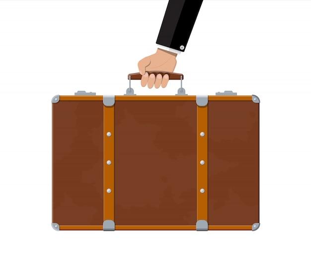手にヴィンテージの古い旅行スーツケース