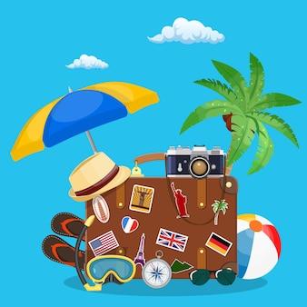 ヴィンテージの古い旅行スーツケース。ステッカー付きレザーレトロバッグ。帽子、写真カメラ、眼鏡、ヤシの木、ビーチサンダル、コンパス。