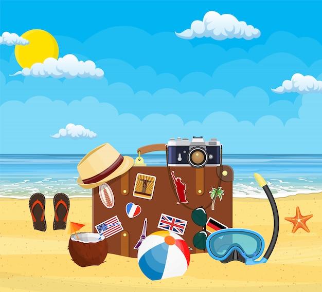 ビーチでヴィンテージの古い旅行スーツケース。