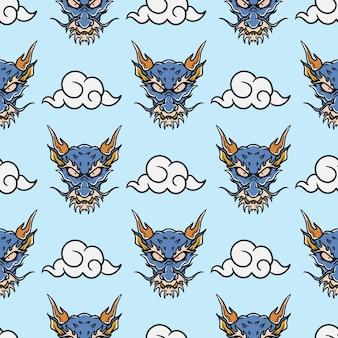 青い背景の上のビンテージスタイルの日本のドラゴンの頭と空の入れ墨のシームレスなパターン