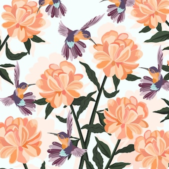 オレンジ色の花の庭で紫のハチドリ