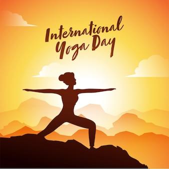 Силуэт представления молодой женщины практикуя virabhadrasana на восходе солнца на горном виде на международный день йоги.