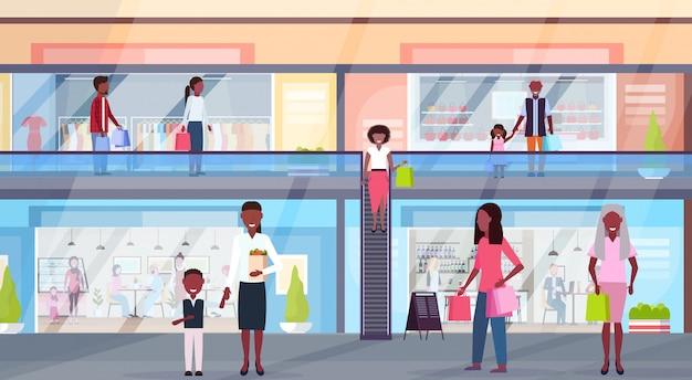 Посетители ходят в современном торговом центре с бутиками одежды и кафе, супермаркет, розничный магазин, интерьер, горизонтальный, полная длина