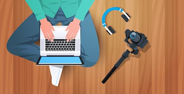 ブロガーや写真家が床に座ってノートパソコンのソーシャルメディアネットワークのブログのコンセプトを編集しているビデオキーボードのトップアングルビューで入力しているvloggerの水平ビュー