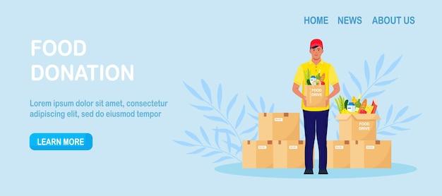 기부 상자를 들고 식료품이 든 패키지를 들고 있는 자원 봉사자. 자선, 빈곤층을 위한 식량 기부