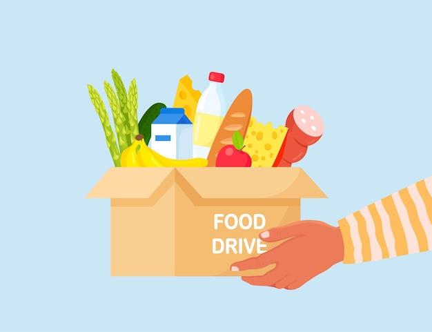 Волонтер держит ящик для пожертвований с едой для голодающих. различные продукты для бездомных в приюте. концепция солидарности и благотворительности