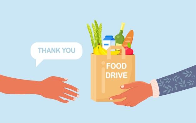Волонтер держит ящик для пожертвований с едой для голодающих. различные продукты для бездомных в приюте.