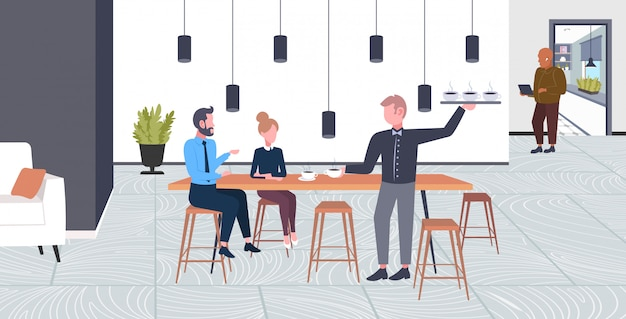Waiter serving drinks to businesspeople couple man woman having break business time coffee point concept  full length modern cafe interior horizontal