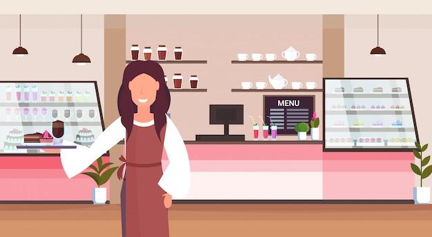 ウェイトレスがトレイを保持しているケーキとカプチーノのコーヒーショップの労働者がクライアントにサービスを提供する笑顔の女性が立っているモダンなカフェテリアインテリア水平漫画のキャラクターの肖像画