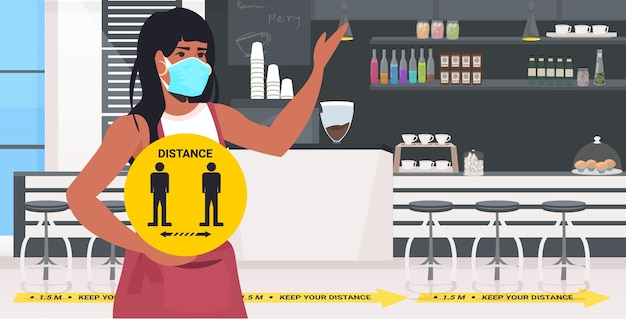 Waitress in mask holding yellow sign keeping distance to prevent coronavirus pandemic cafe interior horizontal portrait