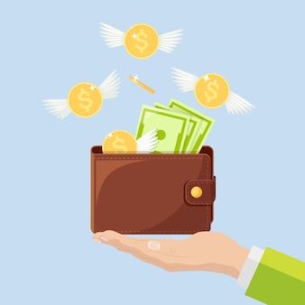 Кошелек с летающими деньгами в руке. золотые монеты с вылетающими крыльями. потеря денег, перерасход