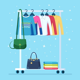 Wardrobe for woman. metal rack with clothes, bags on hangers in boutique. store stand with fashionable outfit. interior of dressing room.