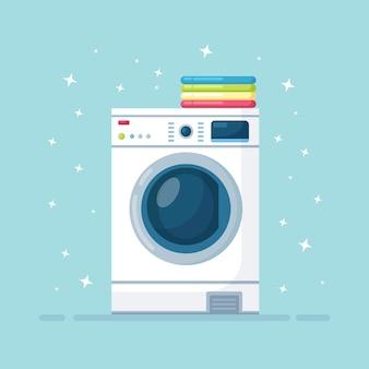 乾いた衣類のスタックを備えた洗濯機。ハウスキーピング用の電子洗濯装置