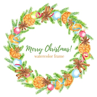 Акварельный рождественский венок с еловыми ветками, апельсинами, звездочками аниса и палочками корицы, елочными шарами и лентами. цветочная рамка