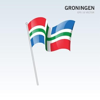 회색 배경에 고립 된 네덜란드의 흐로닝언 지방의 깃발을 흔들며
