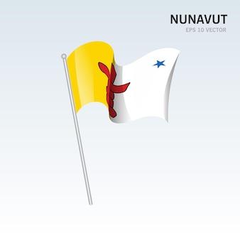 회색 배경에 고립 된 캐나다 누나 부트 준주의 깃발을 흔들며