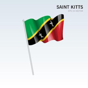 灰色の背景に分離されたセントキッツ島の旗を振る