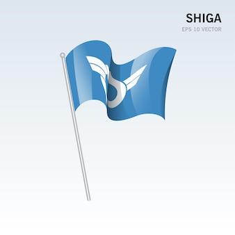 회색 배경에 고립 된 일본 시가 현의 깃발을 흔들며