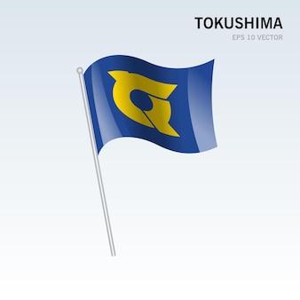 회색 배경에 고립 된 일본의 도쿠시마 현의 깃발을 흔들며