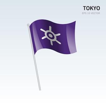 회색 배경에 고립 된 일본 도쿄 현의 깃발을 흔들며