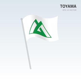 회색 배경에 고립 된 일본의 도야마 현의 깃발을 흔들며