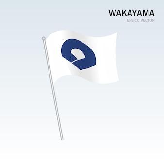 회색 배경에 고립 된 일본 와카야마 현의 깃발을 흔들며