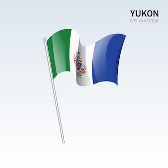 灰色の背景に分離されたカナダのユーコン準州の旗を振る