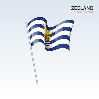 회색 배경에 고립 된 네덜란드의 zeeland 지방의 깃발을 흔들며
