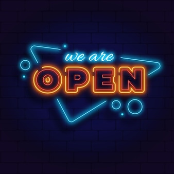 'we are open' neon sign on brick wall